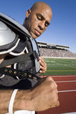 Football player putting pads on Stock Image