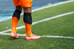 Football Player. `re in orange suite on conner of yard Royalty Free Stock Image