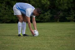 Football player ready to kick the soccer ball. In the ground Royalty Free Stock Photo