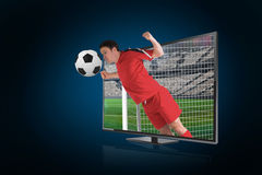 Football player in red heading ball through tv Royalty Free Stock Photo