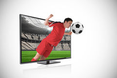 Football player in red heading ball through tv Stock Photos