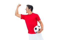 Football player in red holding ball and cheering Stock Images