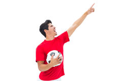 Football player in red holding ball and pointing. On white background Stock Photo