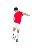 Football player in red kicking ball Stock Image