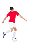 Football player in red kicking ball Royalty Free Stock Photos