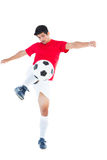 Football player in red kicking ball Stock Photo