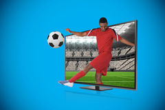 Football player in red kicking Stock Images