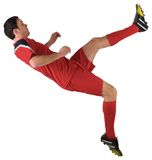 Football player in red kicking Stock Photos