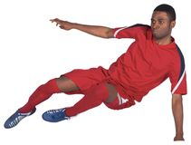 Football player in red kicking. On white background stock photo