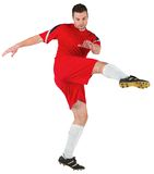 Football player in red kicking Royalty Free Stock Image