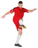 Football player in red kicking Stock Photography