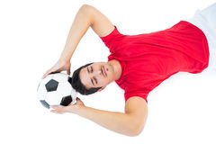 Football player in red lying with ball. On white background Stock Photography