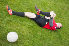 Football player in red lying injured on the pitch Royalty Free Stock Images