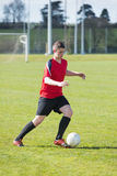 Football player in red playing on pitch Stock Image