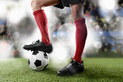 Football player in red socks and black shoes plaing with the ball standing on stadium pitch Royalty Free Stock Photo