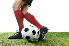 Football player in red socks and black shoes running and dribbling with the ball playing on grass Stock Image