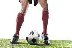 Football player in red socks and black shoes running and dribbling with the ball playing on grass Stock Photos
