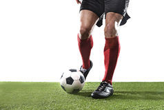 Football player in red socks and black shoes running and dribbling with the ball playing on grass Stock Photo