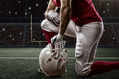 Football Player. With a red uniform on his knees, on a Stadium Stock Image
