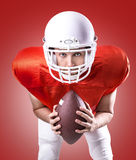Football Player on red uniform on red background Royalty Free Stock Images