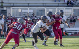 Football Player Running With The Ball. A high school football runs with a ball while his teammates block the opponents stock photography