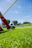 Football player scoring a goal. While playing soccer Royalty Free Stock Images