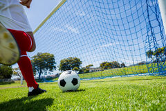 Football player scoring a goal. While playing soccer Royalty Free Stock Image