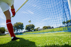 Football player scoring a goal. While playing soccer Royalty Free Stock Photography
