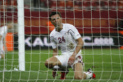 Football player seen through net. Romeo Surdu, player of Rapid Bucharest, shows his disappointment after missing a chance during the match between his team and Stock Photo