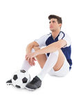 Football player sitting on the ground with ball. On white background stock photo