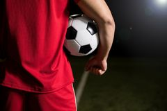 Football player with soccer ball. Cropped rear view of a young football player in red uniform holding the ball under his arms at stadium Stock Images