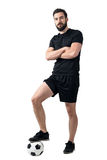 Football player standing on the ball with one leg posing with crossed arms Royalty Free Stock Photo
