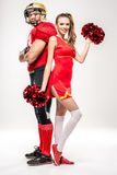 Football player standing with cheerleader Royalty Free Stock Photos