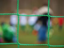 Football player stands against goal with net and stadium. Football gate net. Soccer gate. Net.  In blurry background stand people Royalty Free Stock Photos