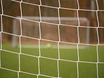 Football player stands against goal with net and stadium. Football gate net. Soccer gate. Net.  In blurry background stand people Stock Photos