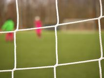Football player stands against goal with net and stadium. Football gate net. Soccer gate. Net.  In blurry background stand people Stock Image
