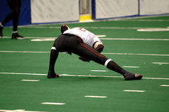 Football player stretch. American football player on field stretching royalty free stock photography