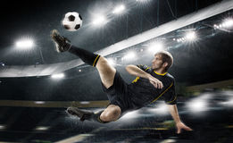 Football player striking the ball. Football player in red shirt striking the ball Stock Photo