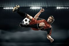 Football player striking the ball. Football player in red shirt striking the ball royalty free stock photo
