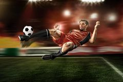 Football player striking the ball. Football player in red shirt striking the ball royalty free stock images