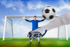 Football player striking ball at goalkeeper Stock Photos