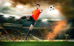 Football player striking the ball at the stadium. Football player in orange shirt striking the ball at the stadium Stock Photos