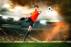 Football player striking the ball at the stadium Stock Photos