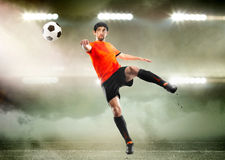 Football player striking the ball at the stadium. Football player in orange shirt striking the ball at the stadium Royalty Free Stock Photography