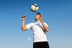 Football player striking the ball at the stadium Stock Images