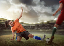 Football player tackling for the ball. Against other team Royalty Free Stock Images