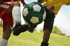 Football Player Tackling Soccer Ball. Midsection of two multiethnic player kicking soccer ball Royalty Free Stock Photography