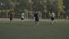 Footballer failing to score goal after penalty kick. Football player taking a penalty kick and failing to score a goal, with ball hitting goalpost during soccer stock video footage