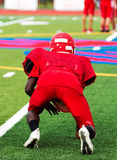 Football player in three point stance at practice. A high school football player at practice in a three point stance on a green turf field in all red clothing Stock Images