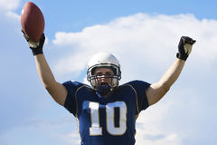 Football Player Touchdown. A football players raises his arms in celebration after scoring a touchdown royalty free stock image
